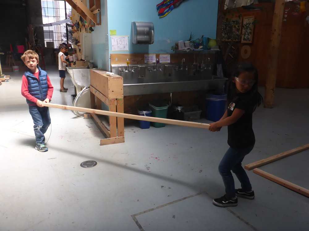 Zeke and Dany carefully cary a LOOONG piece of wood for the train tracks back over to their project area. Great teamwork!