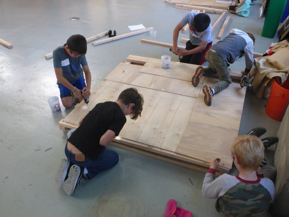 The train group ended up with a plan to quilt together scrap pieces of plywood to cover the floors of their train cars. Great work-around, and they look cool too!