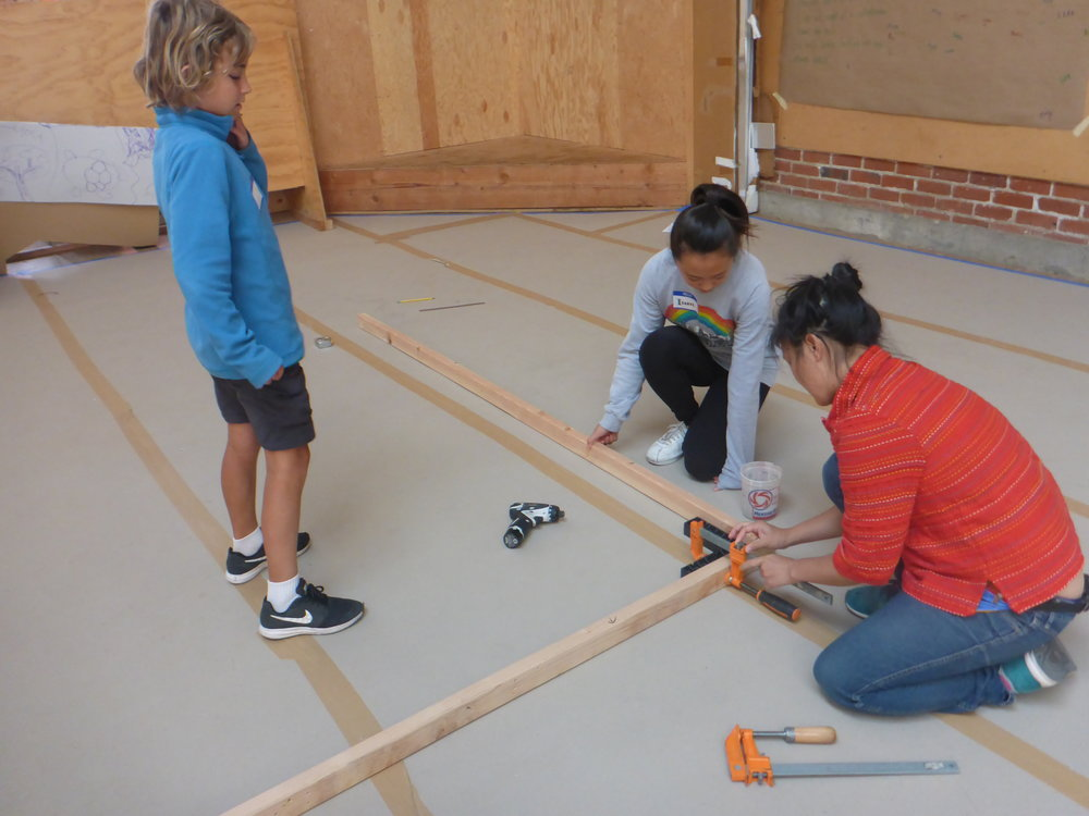 Nikki helps Isabel and Silas use a carpenter's square to clamp two pieces of wood together at a nice 90d corner.