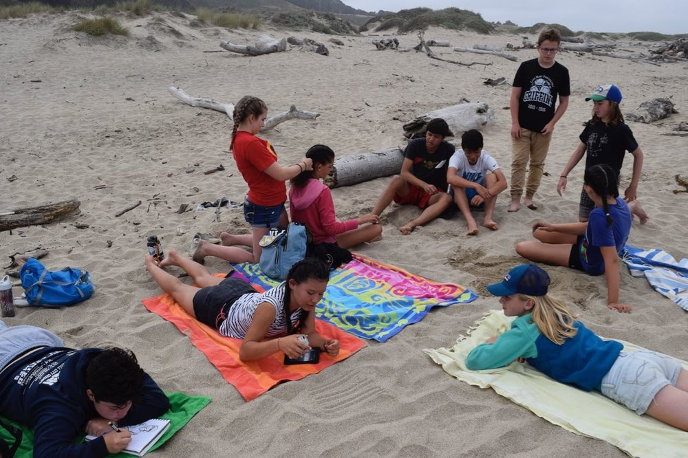 We put down our towels and chillax in our own ways - drawing, reading, braiding hair and digging holes in the sand to name a few.