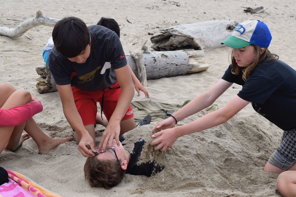 Reilly volunteers to be burried in the sand by Ethan and Oliver.