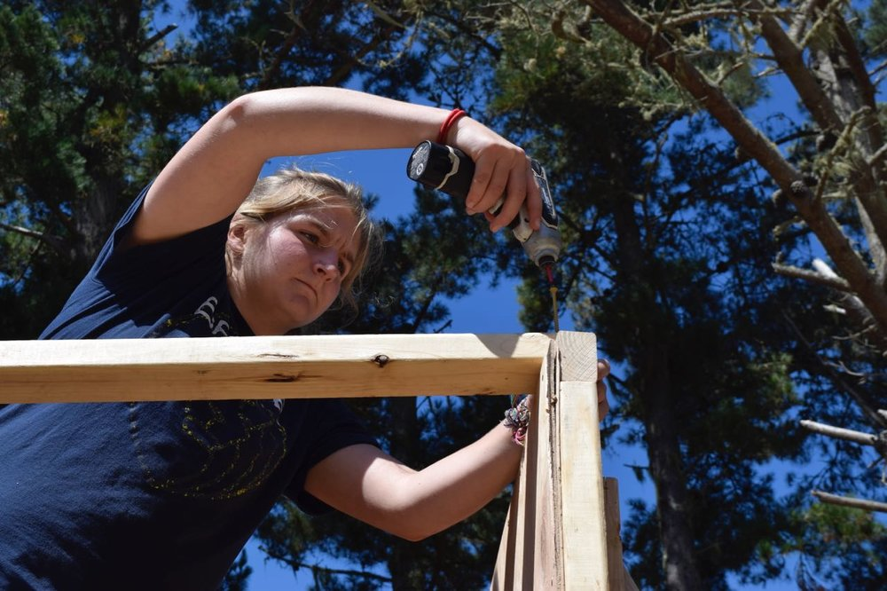 Sarah P. secures a plank atop 2 walls to prevent them from falling.