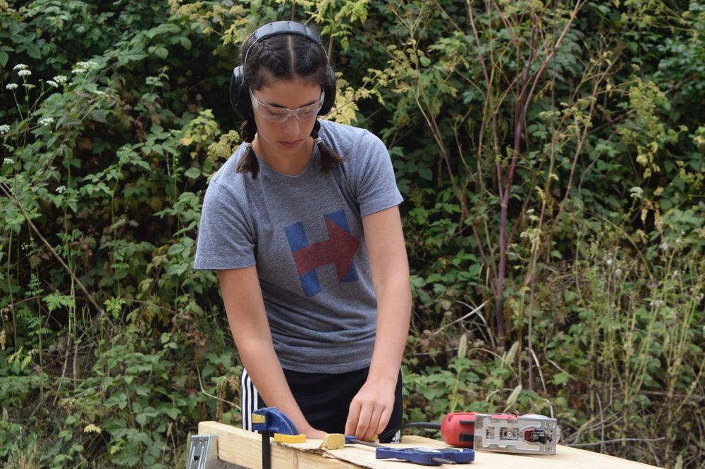 Noa clamps down a piece of plywood to jigsaw off sides for a lock box.