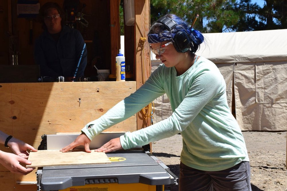Blueberry tries out the table saw for the first time to cut a bottom for a pulley-powered basket.