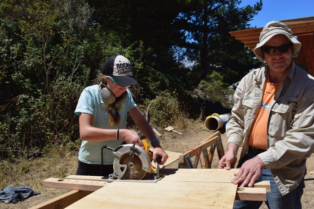 Madelyn mastering the art of the circular saw with some tips from Gever.