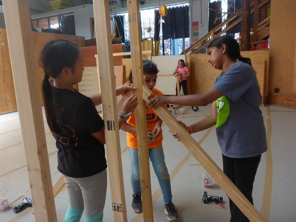 Sareena, Katerina and Myla work on installing the legs to hold up their fly's climbing wall.