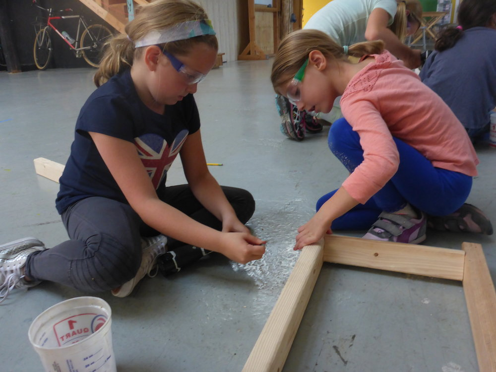 Ava and Emily work on mounting the bars for the crabby-bars. The team thought the bars should be mounted at an angle so they would be easier for a crab's claws to grab. But, this meant they couldn't clamp them on using the carpenter's squares. So, they had to come up with a different way to hold everything together!