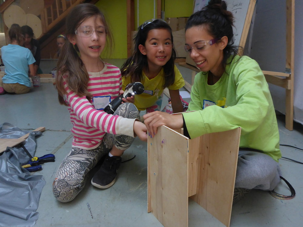 Makarem helps Lainey hold a few pieces of plywood together while she works on her crab--of course!