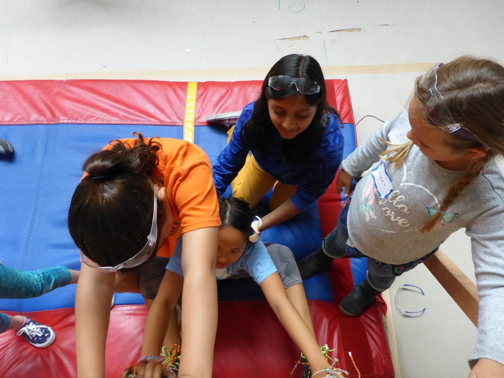 Katerina, Sareena and Violet help Myla get started climbing the fly wall--with velcro attached to her hands and feet!