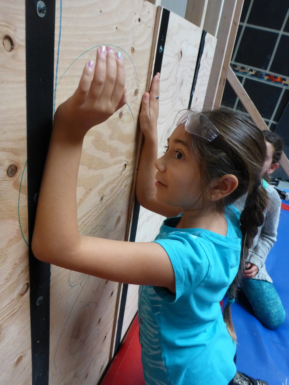 Xochi demonstrates how elbow pads might help distribute weight on the flywall across a few more points of contact. Industrial velcro is rated to hold 10 pounds, so we're operating on the assumption that each point on our body that is stuck to the wall should be able to support 10 pounds. Which means that we'll probably need more than four points of contact!
