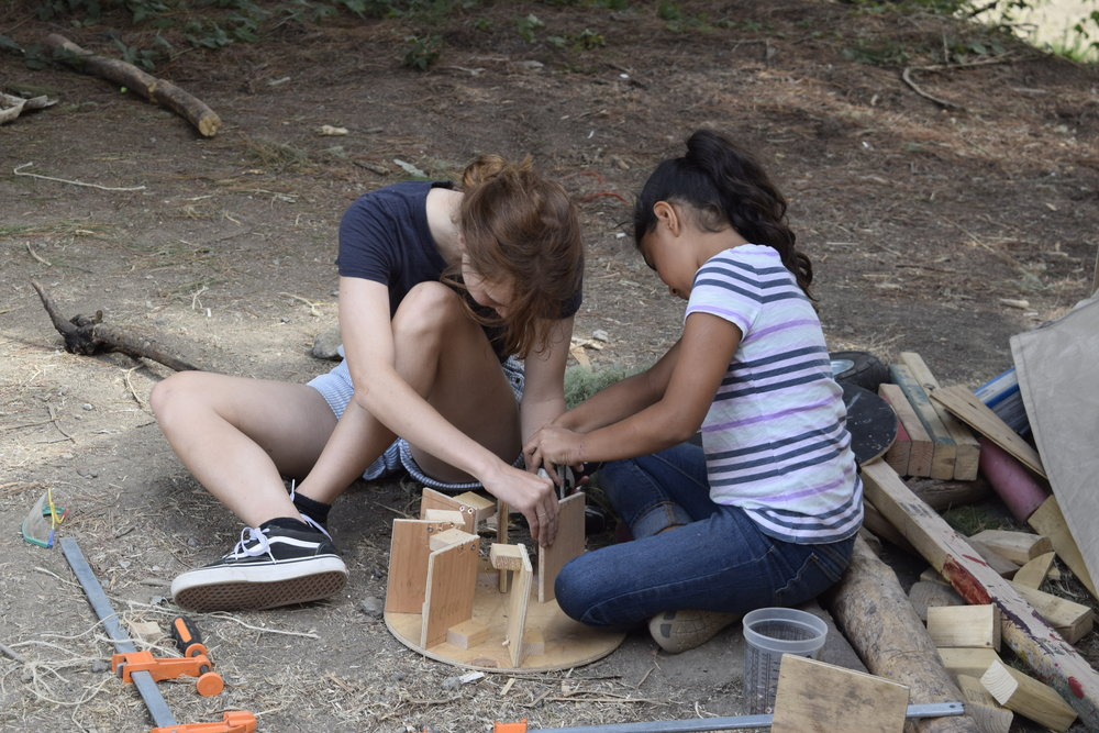 Frannie and Isabella building the waterwheel for the hydropower team.