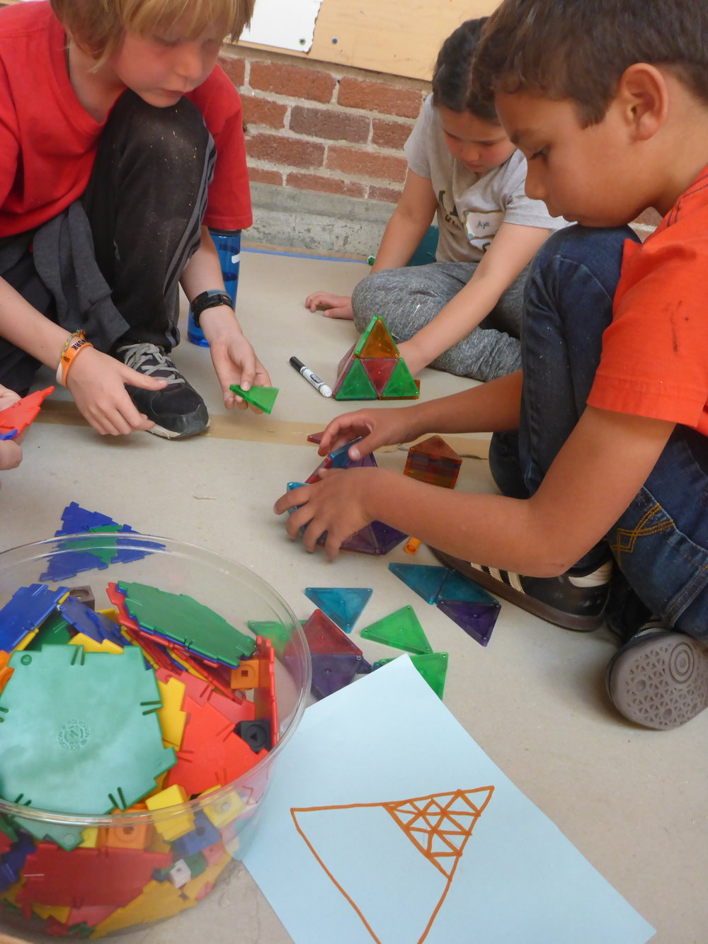 Jasper, Aya and Cole work on turning their drawing into a 3-D shape using magnatiles and polydrons.