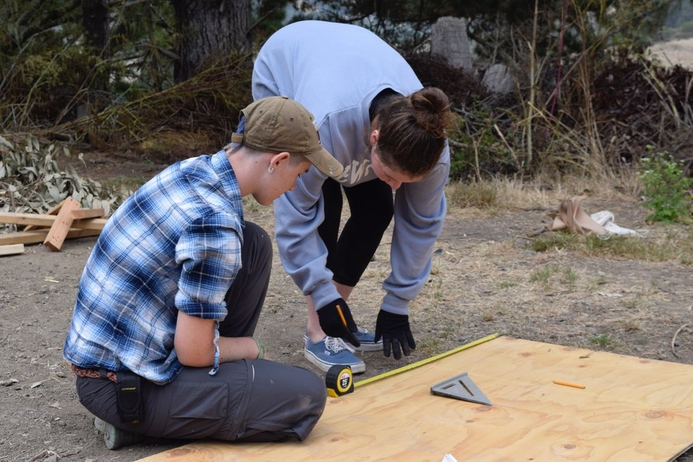 Lily and Emma work on cutting plywood for Nooi's cart.