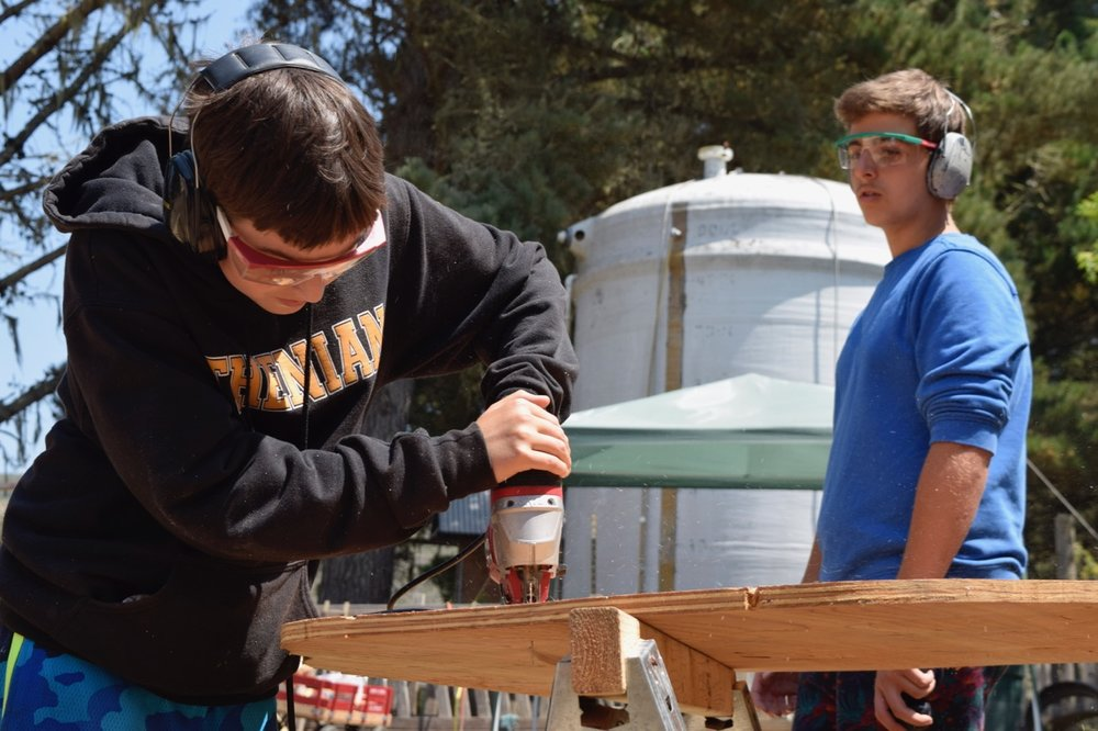 Yoel watches as Ben cuts out the base of their boat-cart.