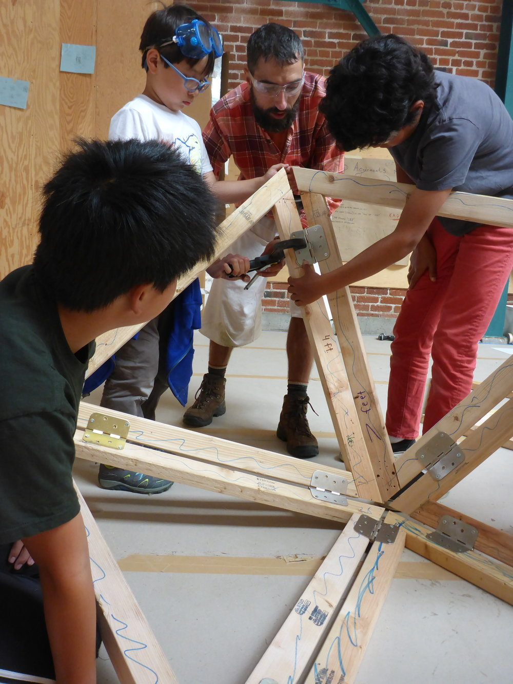 Peter, Ryan, Nathan and Cole hold the dome up in place in order to place a hinge.