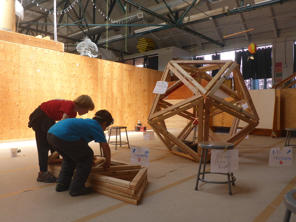 Jasper and Ryan add triangles to the stack, with the first completed icosahedron in the background.