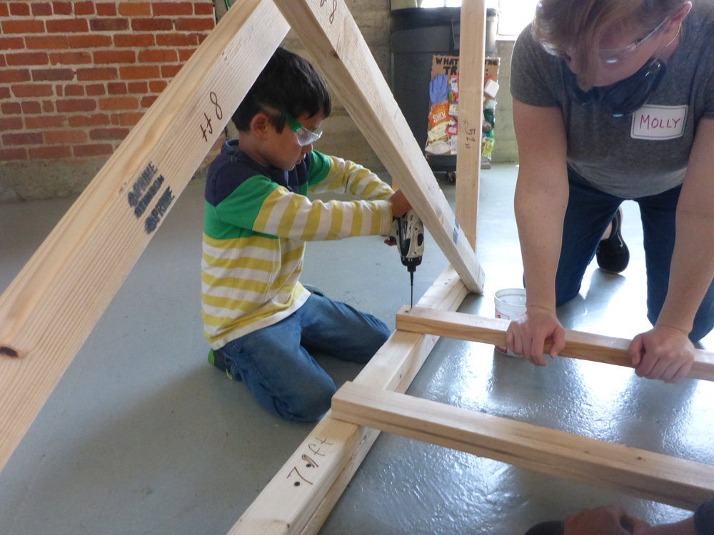 Molly helps Jayden install a few pieces  that hold together a few extra bridge supports.