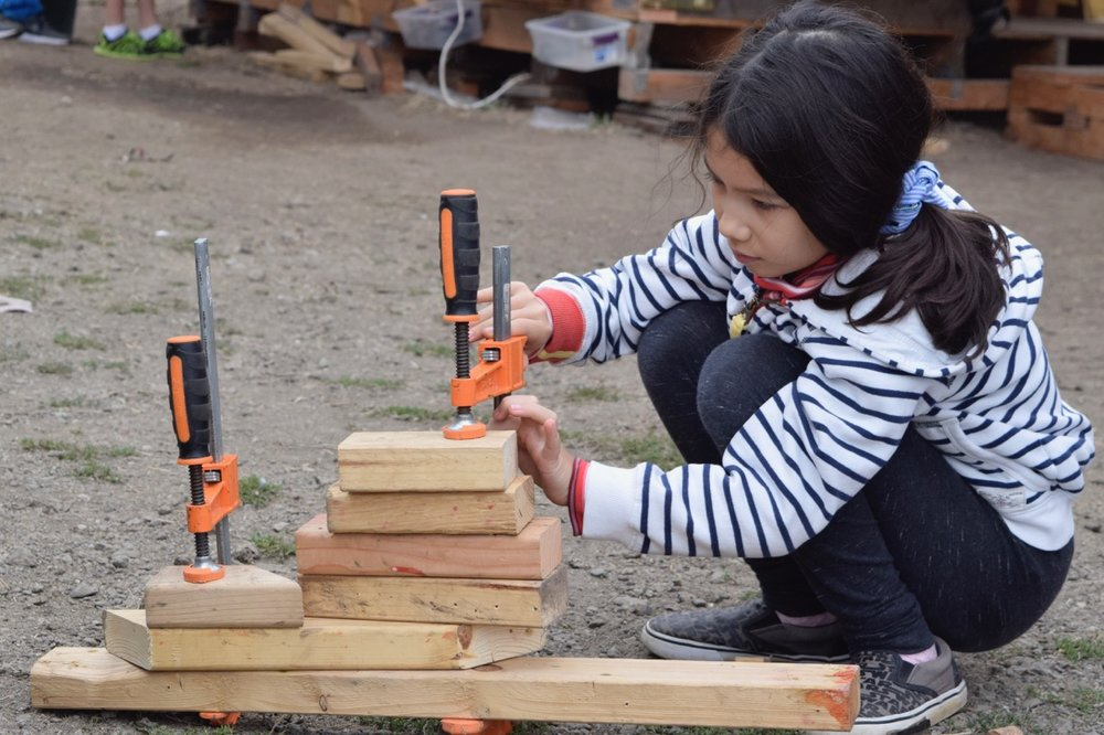 Kiana uses some clamps to stack 7 pieces of wood.