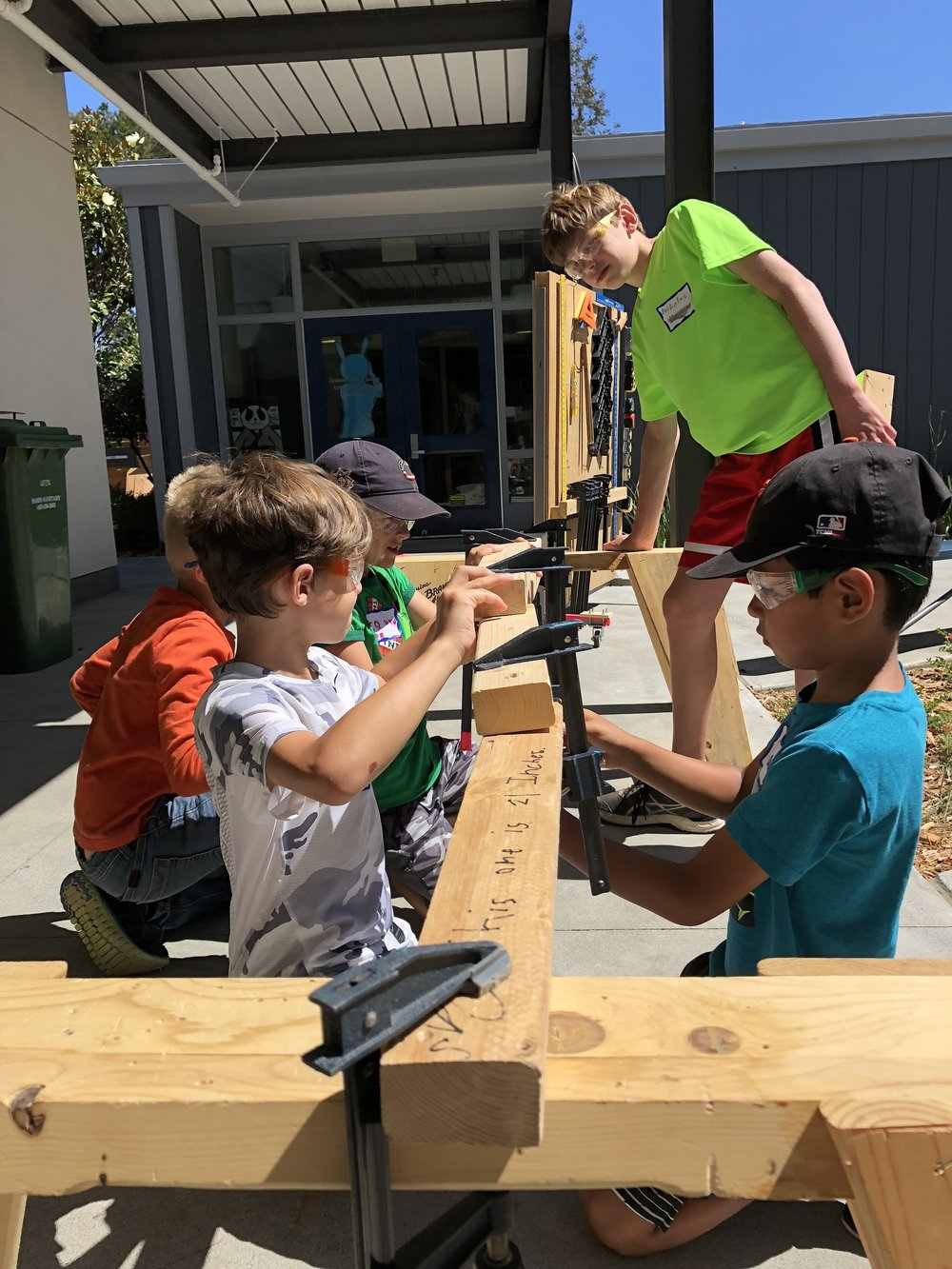During clamp training, students were challenged to build a bridge to span a distance. Teamwork was essential with one person holding the wood and one person operating the clamp.