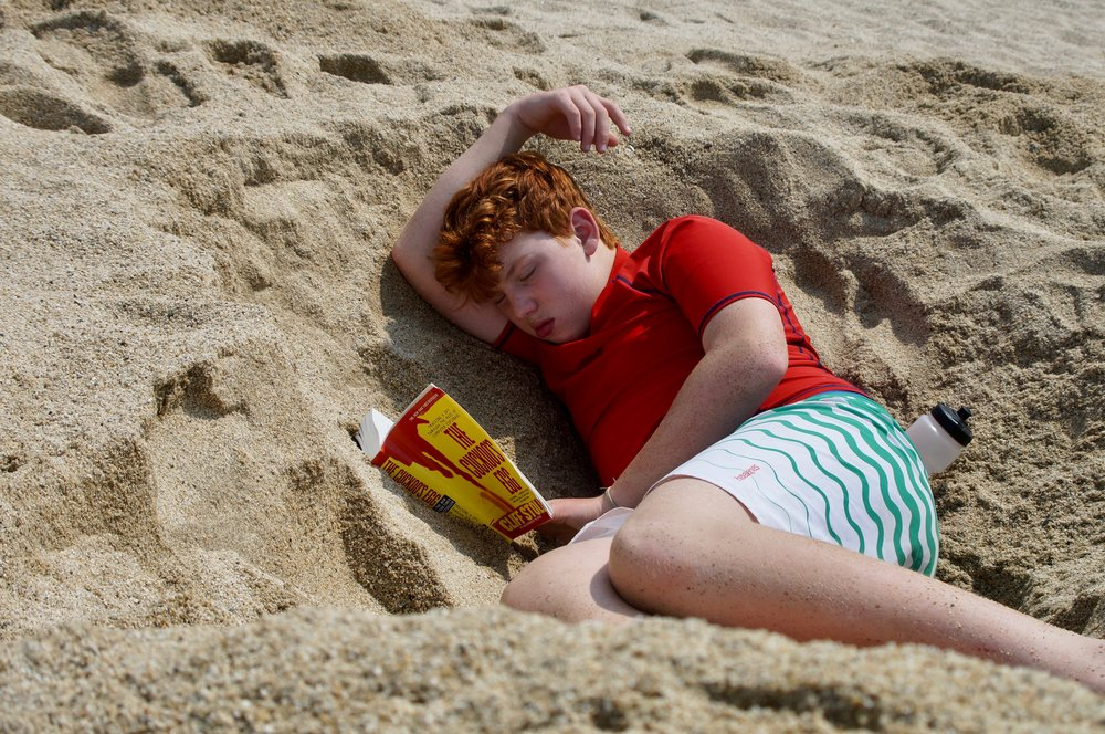 Ryan takes a nap with his book in his hand dug hole.