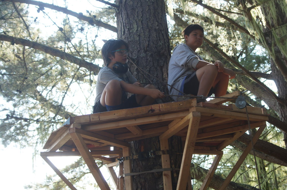 Alex and Evan sit in the treehouse.