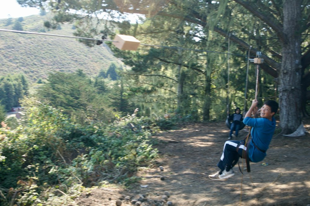 Evan joyfully riding the zip-line.