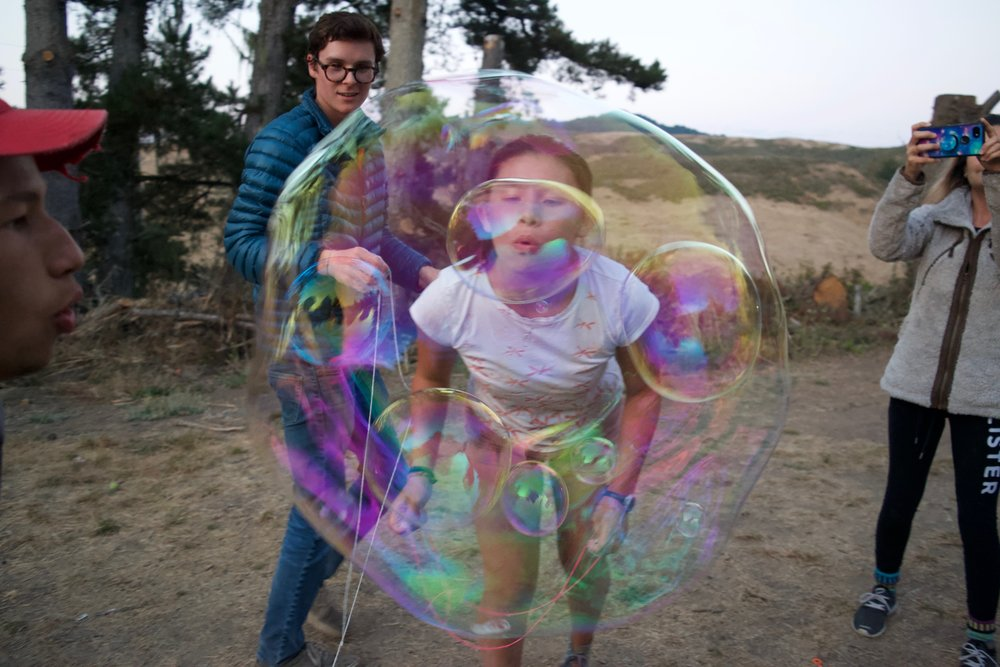 Elijah and Lauren blow bubbles inside a bubble.
