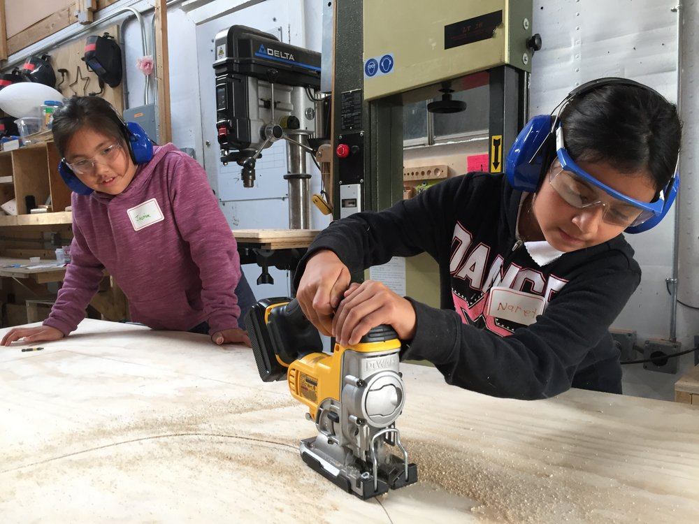 Naret was excited to use a jig saw for the first time! She and Jasmine cut out a circle hatch out of the floor for riders to enter the rocket through.