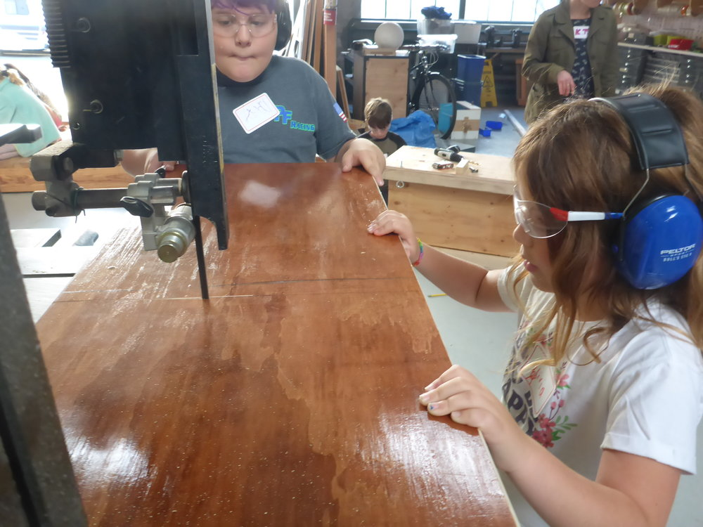Olivia was excited to use the band saw! It's tricky to keep the blade moving along a line, but with her sharp eye, she made some super precise cuts to make pieces for her chair.