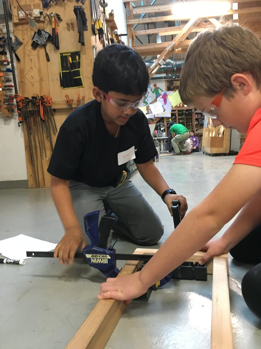 Niam and Conrad use clamps and squares to make a sturdy frame.
