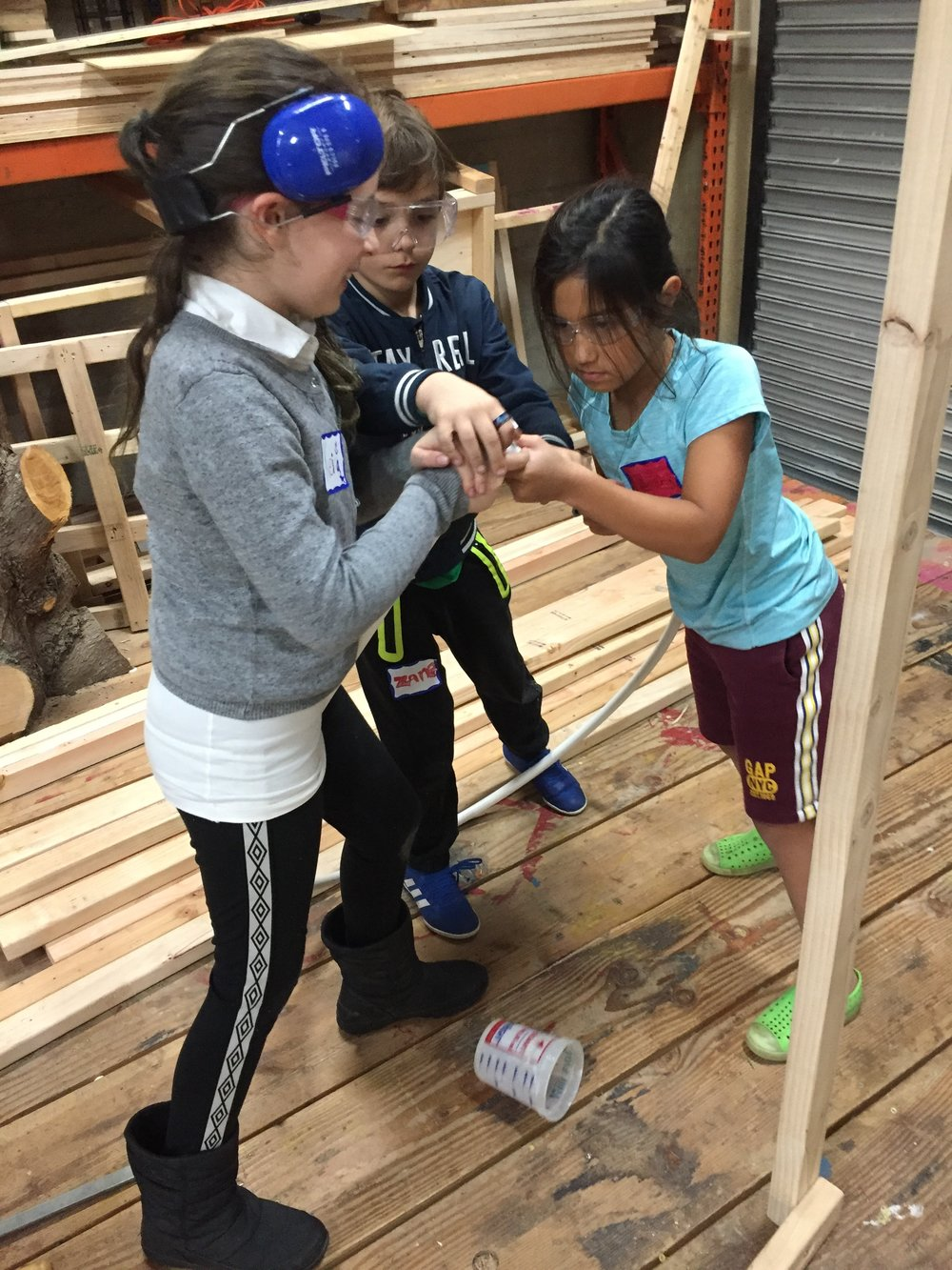 Keira, Zane, and Ayana use their collective strength to bend PVC pipe into the shape of a volcano.