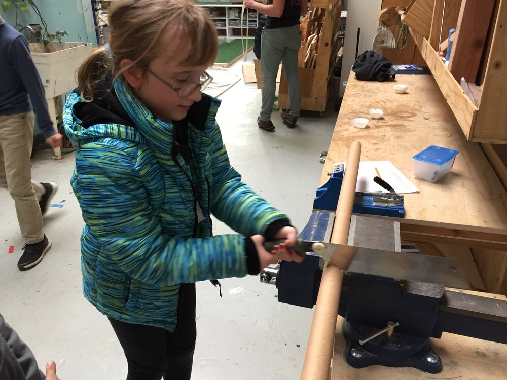 Ava uses a hacksaw (for the first time!) to cut cardboard tubing for her putter.