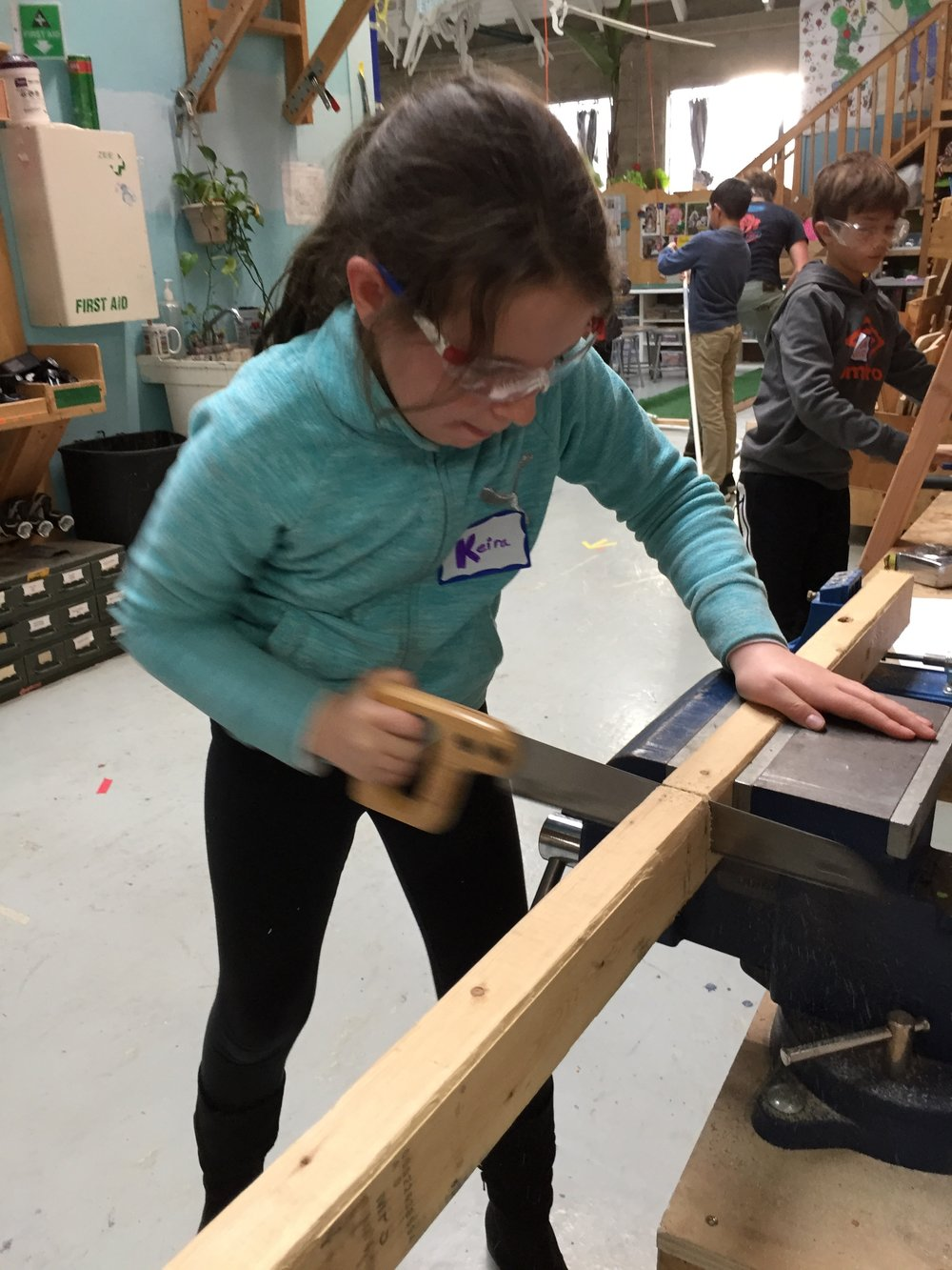 Keira uses the handsaw to cut more structural supports.
