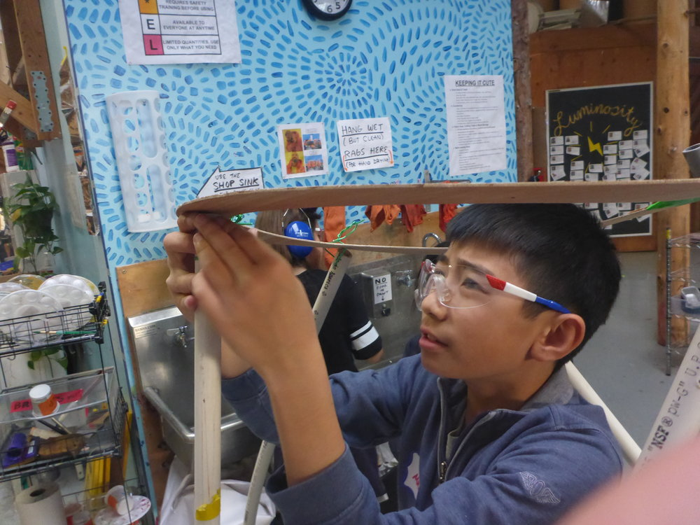 Matthew uses aluminum wire to attach the PVC frame of the volcano.