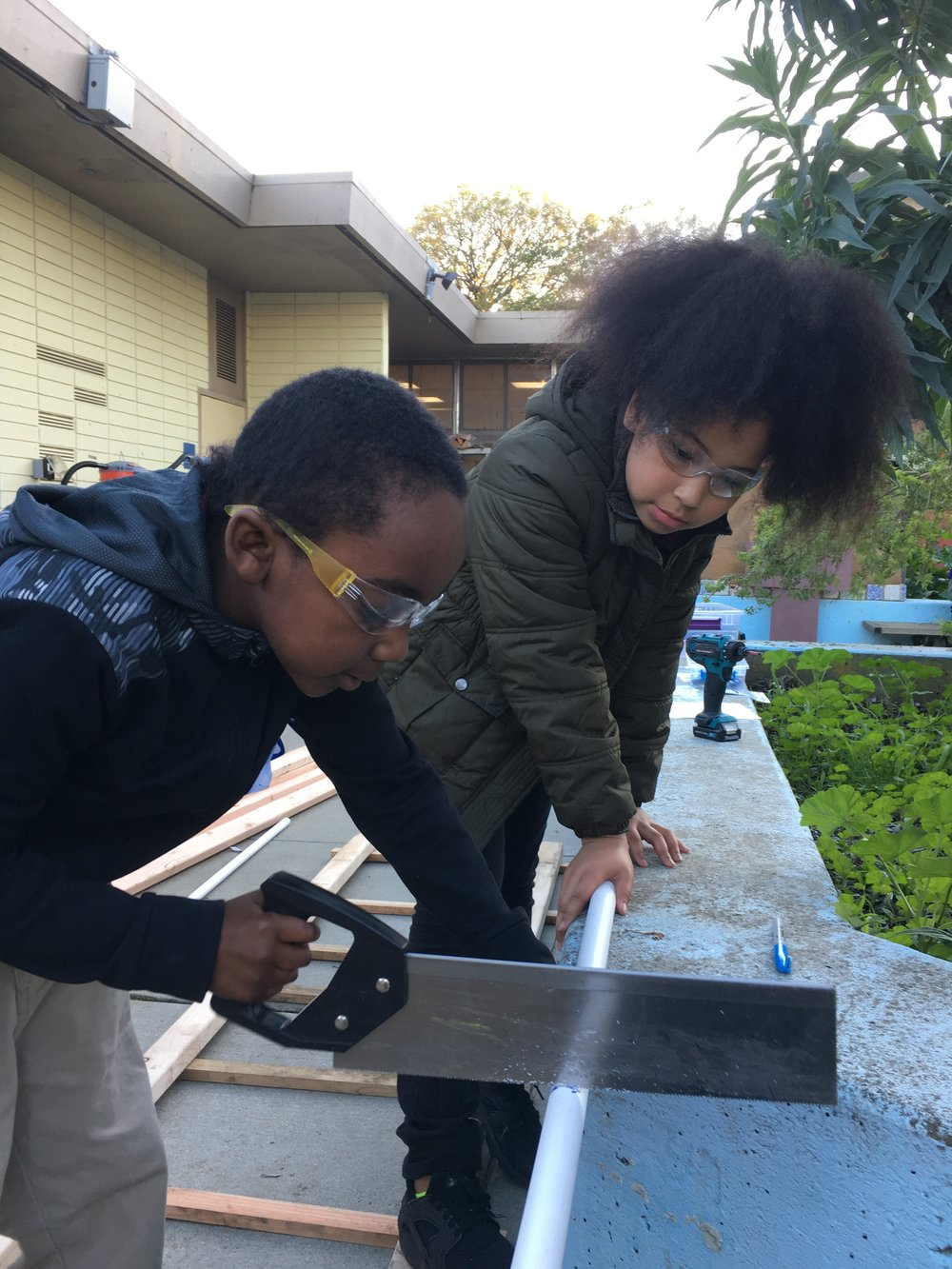 Jayden and MauRae used hand saws for the first time to cut PVC pipe.