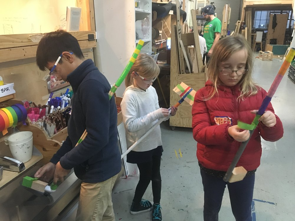 Matthew, Audrey, and Ava use tape to do the final decorations on their putters.