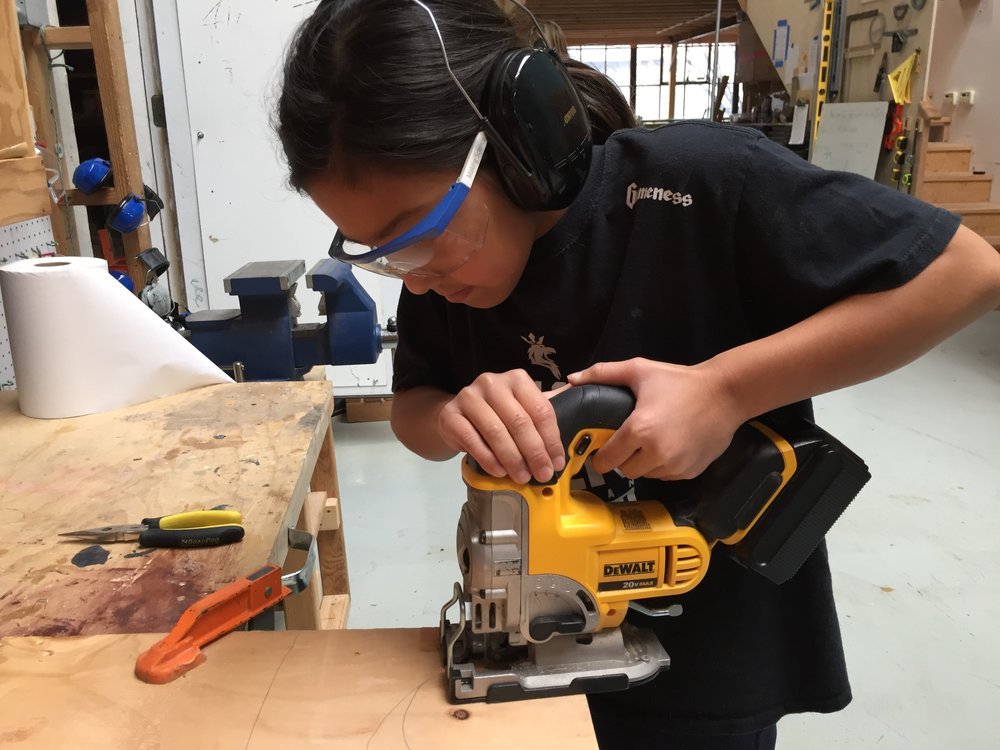 Ayana uses the jig saw to cut pieces for the base of the volcano.