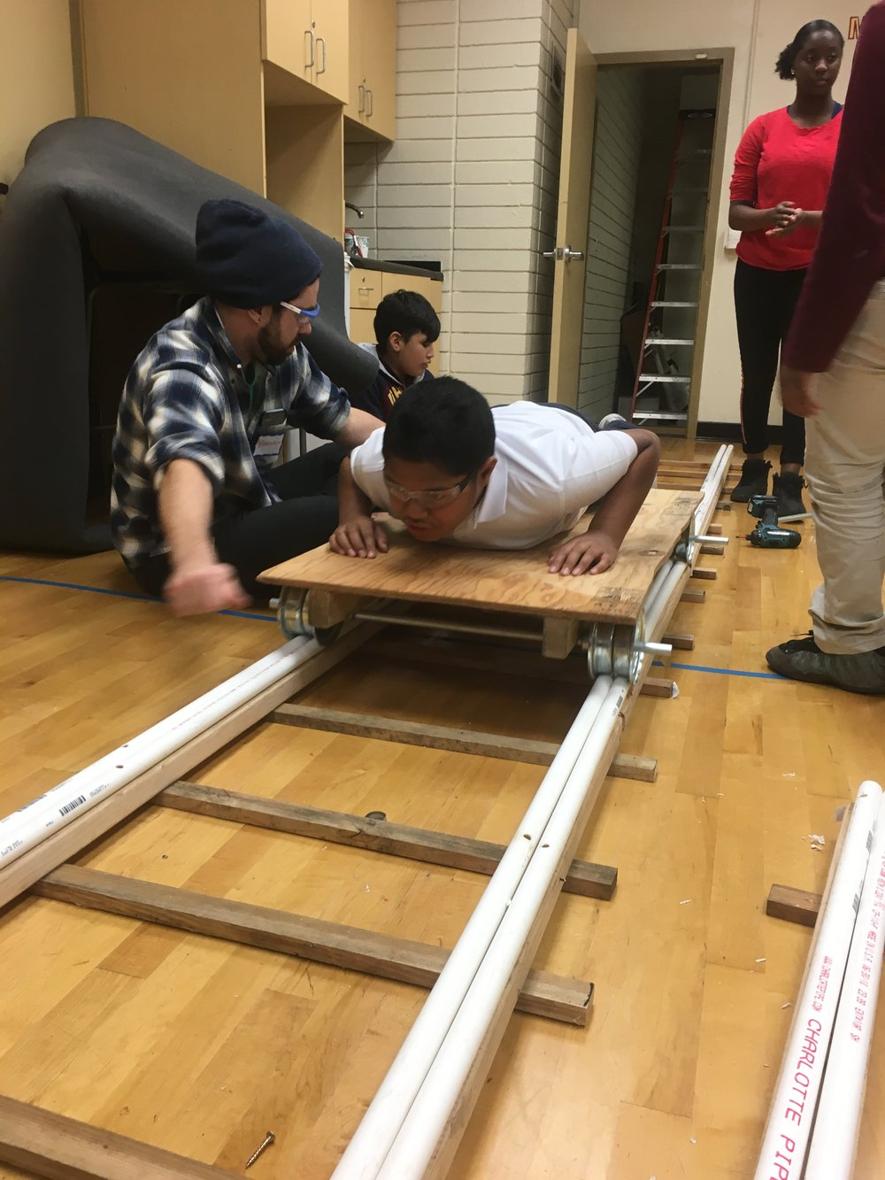 Several members of the group work together to build the bottom of the train car and test it on the tracks… you can tell by Weismann's smile that it works!!