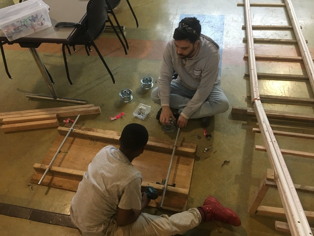 Mekai and Brendon modify the wheels and axles of the train car to fit the PVC pipe rails more accurately. Now it's ready to ride!!!