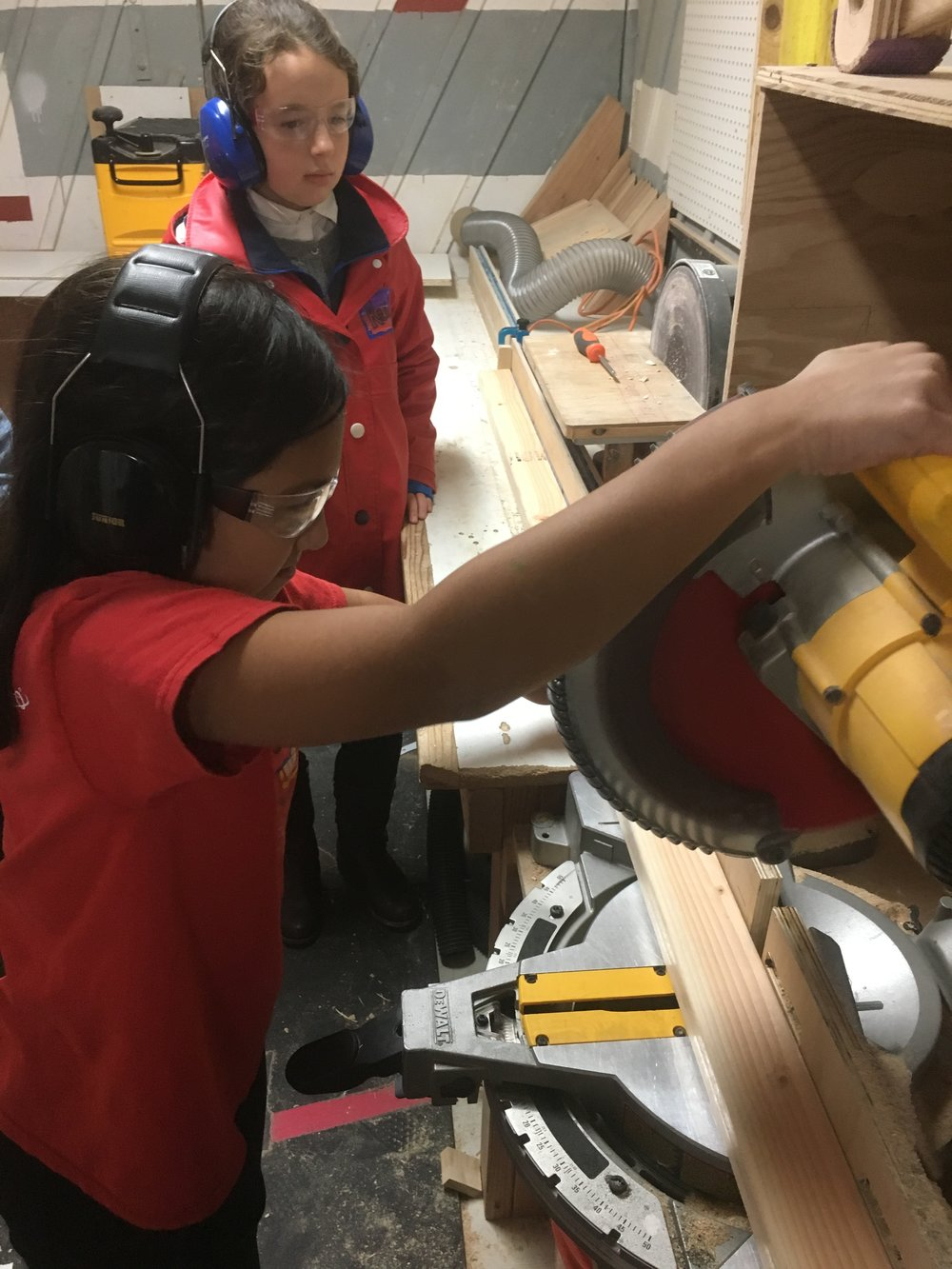 Ayana and Keira in the chopsaw room cutting pieces for the next part of their project.