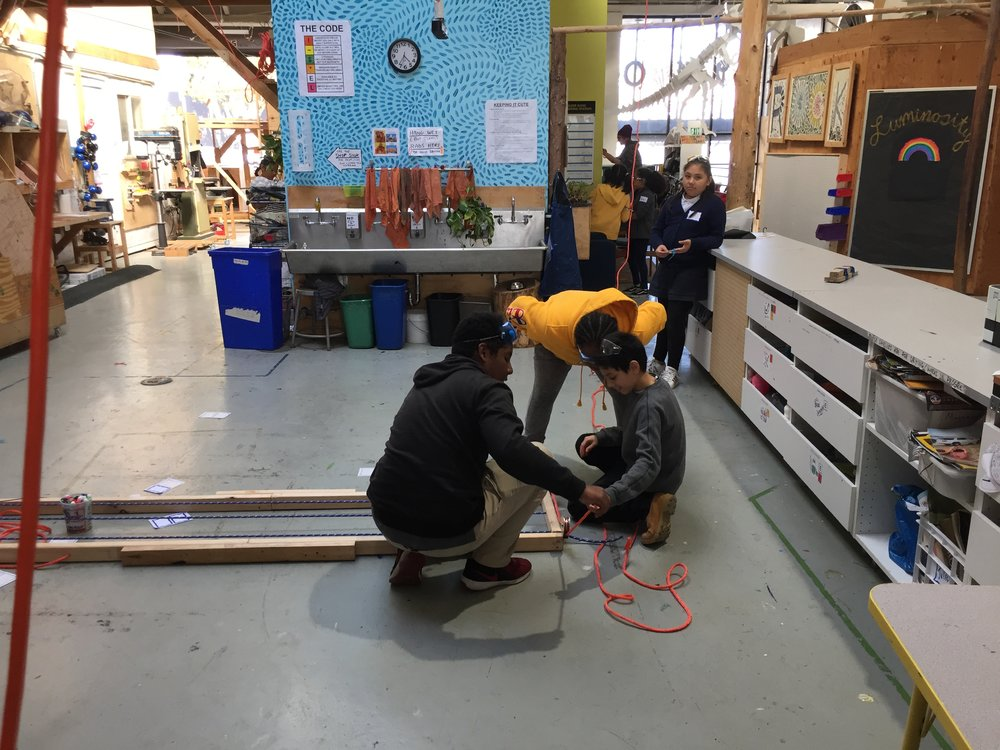 Vassidy, Anthony, and Erick work on installing the Boss Toss pulley.