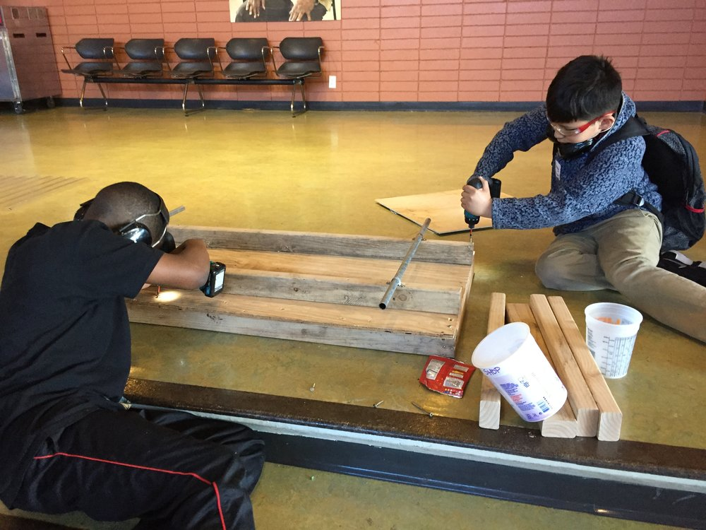 MaKai and Anthony make adjustments to the base of the train car.