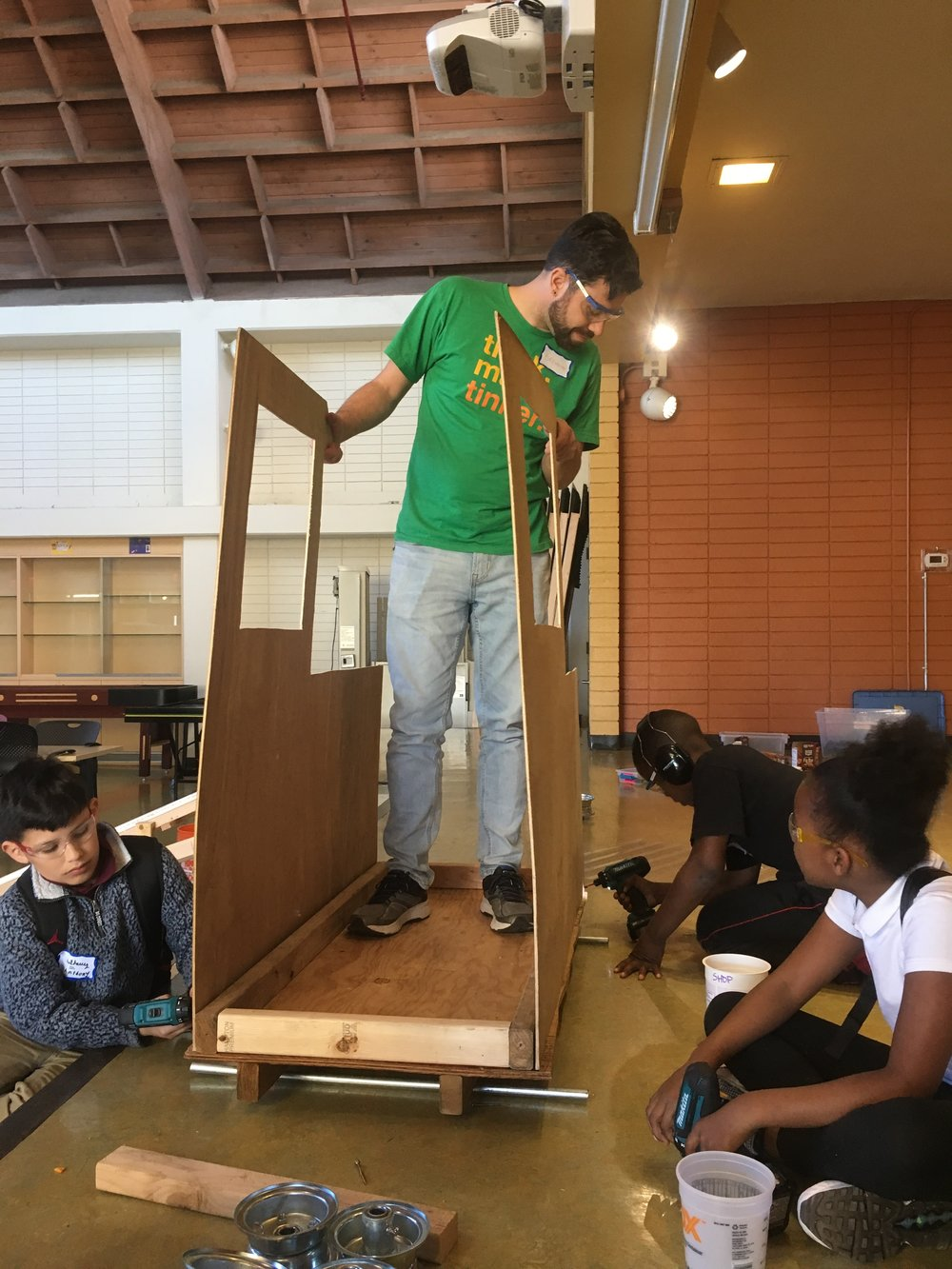 The train car is coming together! The whole group works on it together while Brendon holds the sides in place.