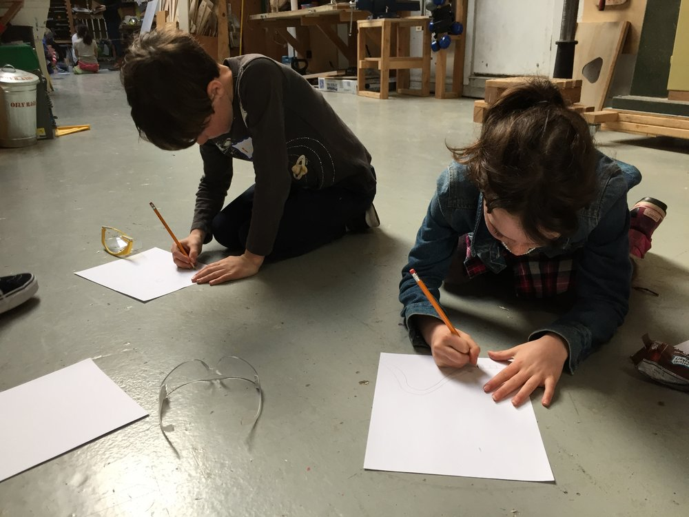 Bear and Willa draw out possible designs for the train accessory group.