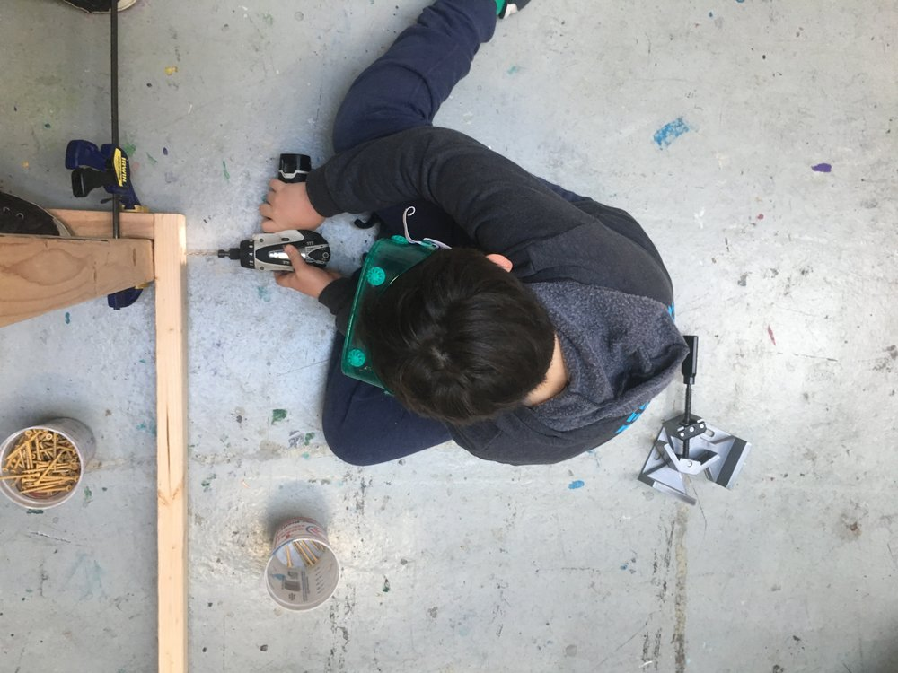 Elliot works on attaching the final screws for the first train car's frame.