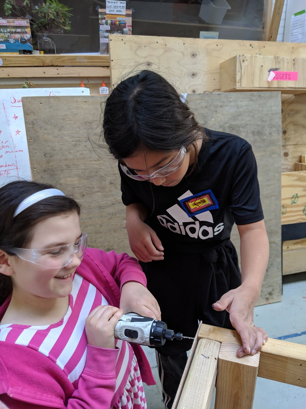 Lily and Ayana put the plywood sides onto their first train car.