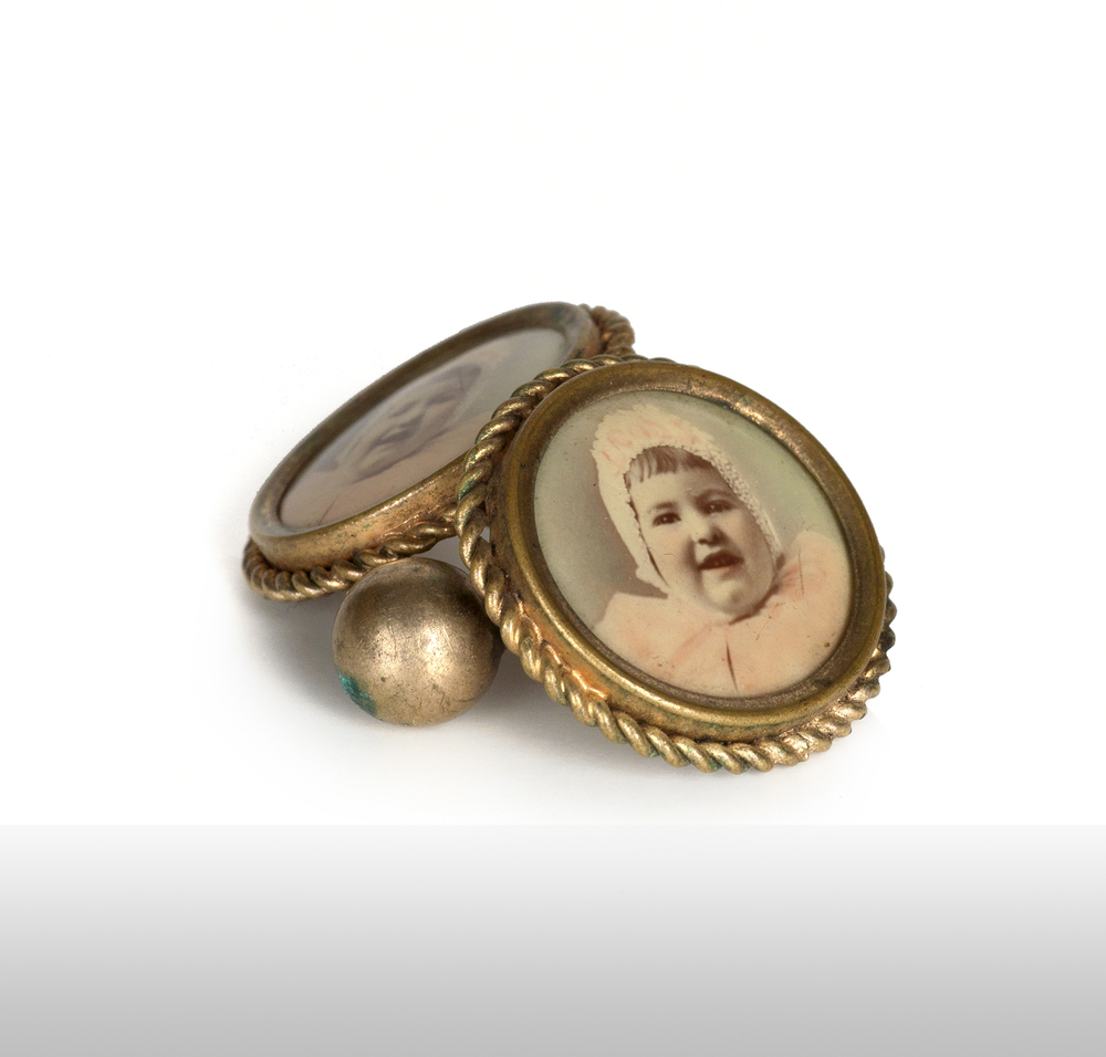 Cuff links with celluloid photographs of a baby. 1910s