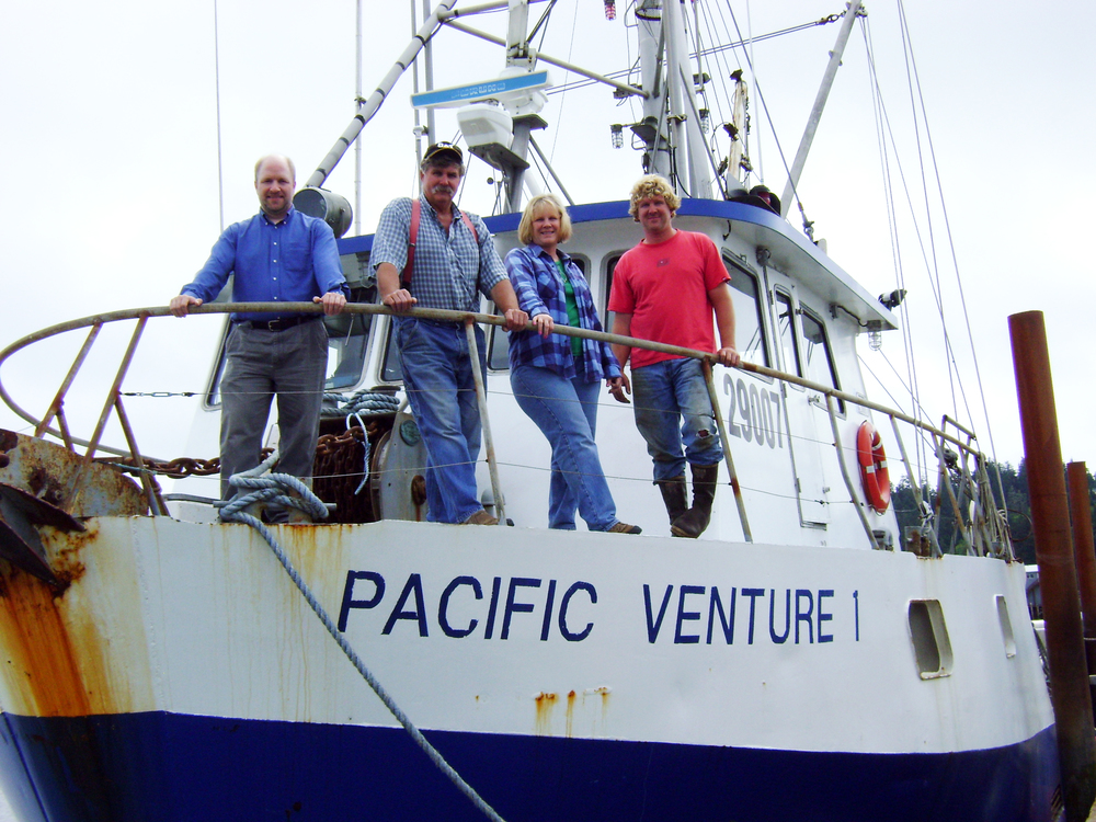 Four people standing on the deck of a boat. Photo Credit: Craft3