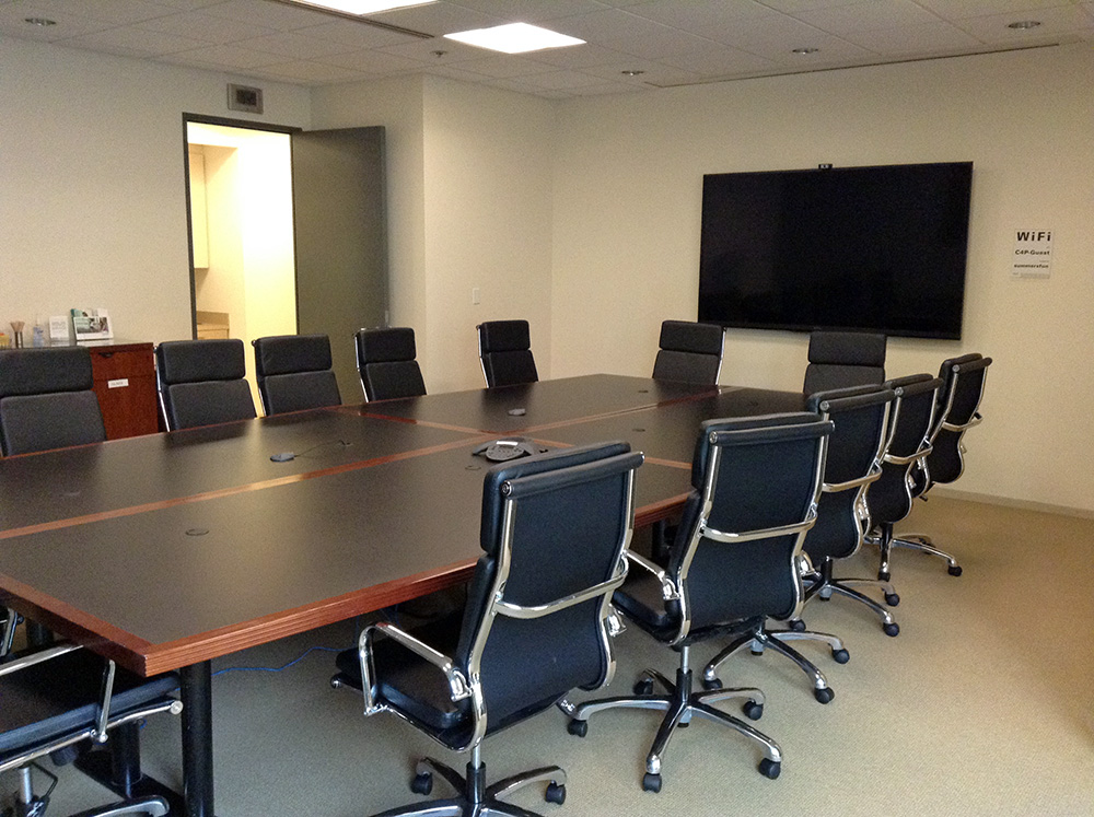 A long conference table with chairs around it. A flatscreen tv hangs on the wall at the head of the table.