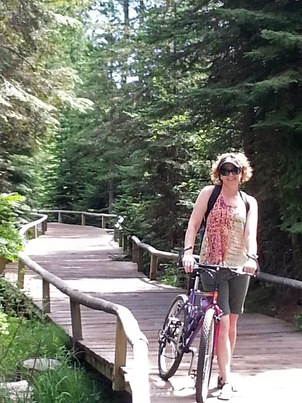 Renée with a  bike on a wooden walkway surrounded by trees.